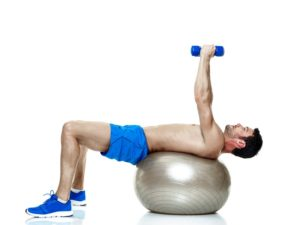 Physio Studio man on swiss ball with dumbbells