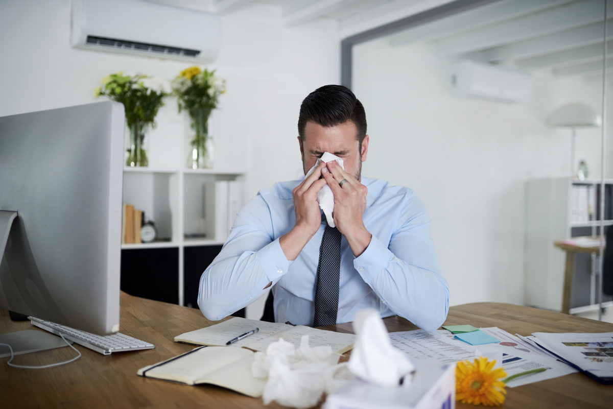 No sick days left man blowing nose