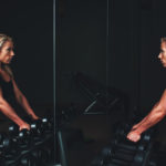 woman with dumbbells looking in mirror